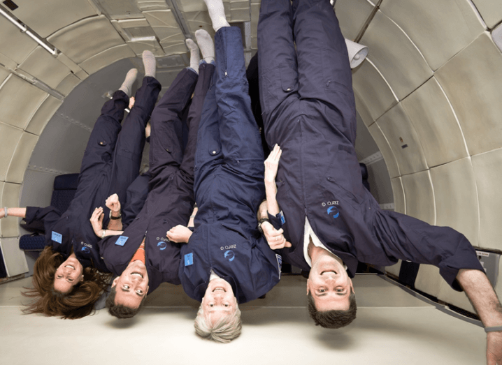 Three men and one woman wearing navy Zero G jumpsuits floating upside down in the interior of an aeroplane.