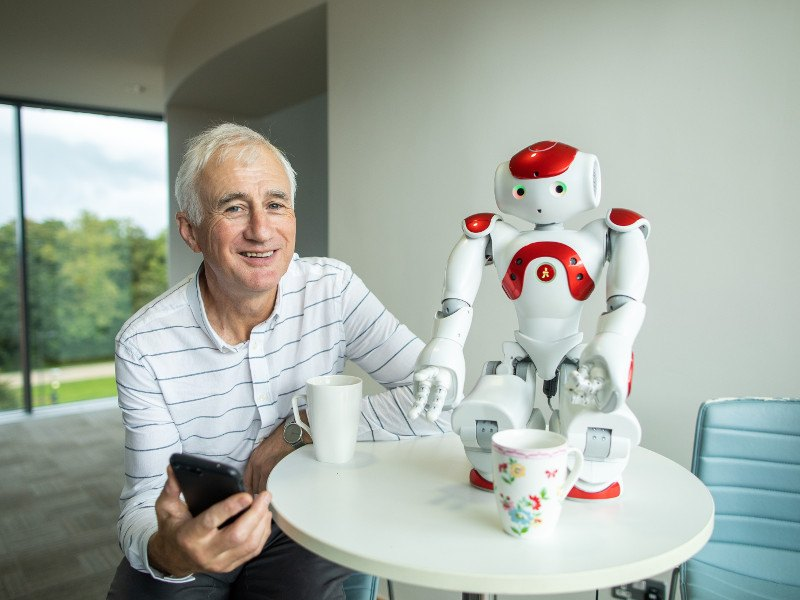 Man in stripy shirt holding smartphone beside a robot.