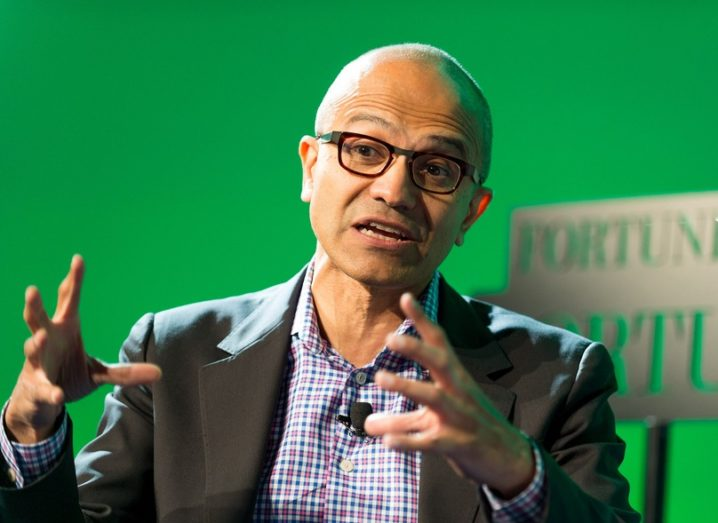 Microsoft CEO Satya Nadella gesticulating at a talk, wearing a blazer, shirt and glasses, against bright green background.