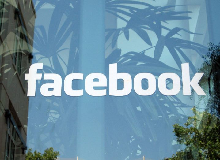 The Facebook logo on a glass panel with indoor plants growing in an office in the background.