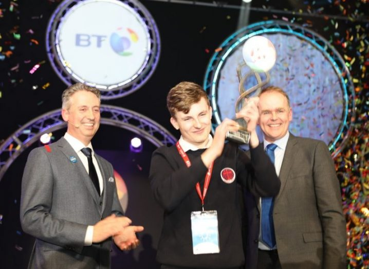 BT Young Scientist winner Adam Kelly holds his trophy aloft as confetti pours down on him.