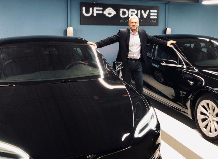 Man in dark jacket, white shirt standing between Tesla electric vehicles.