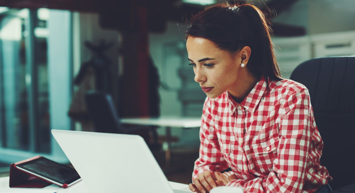 A woman in a red checked shirt sitting at a desk and staring intently at her laptop while working.