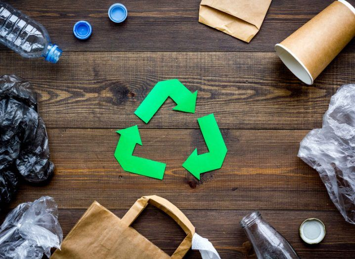 Discarded bags, bottles and disposable cups surround a paper cut-out recycling logo.