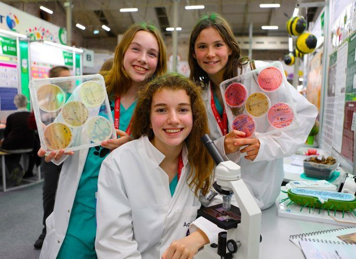 Three girls in lab coats holding bacteria sample boards with a microscope in the foreground.