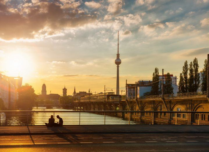 A view of Berlin with sun rising under a blue sky.