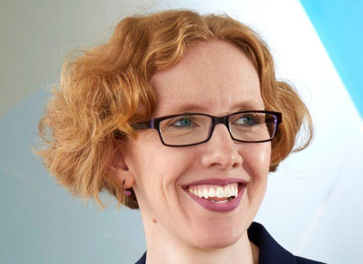 A smiling woman with short red hair and glasses.