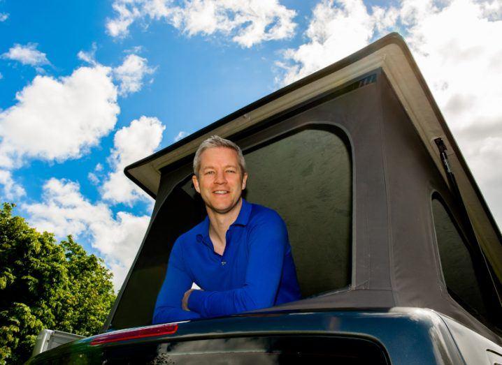 Man in blue jumper looks out of top of camper van under cloudy blue sky.