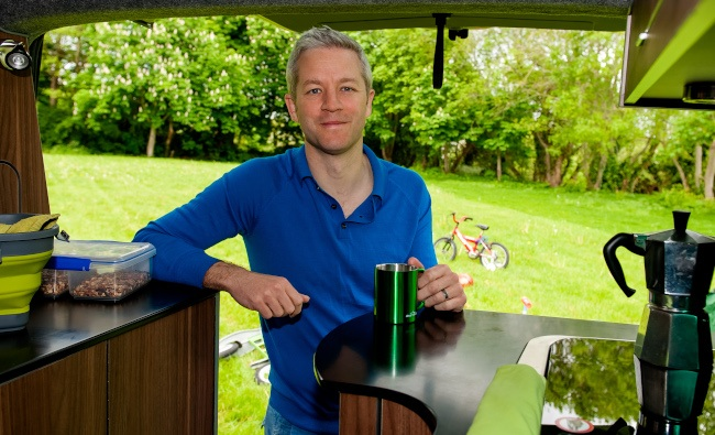 Man in blue jumper with coffee under awning of a tent in campsite.