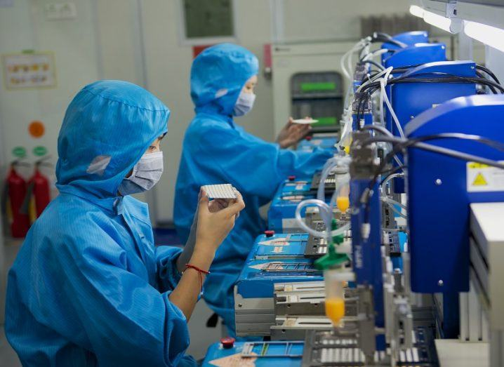 Two people in blue hazard suits assembling electronics in a Chinese factory.
