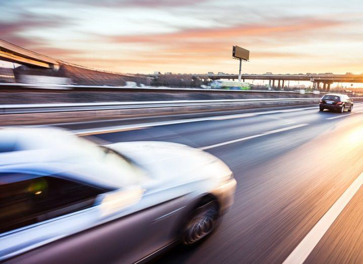 Blurry shot of a car travelling fast on a motorway with a car further ahead of it.