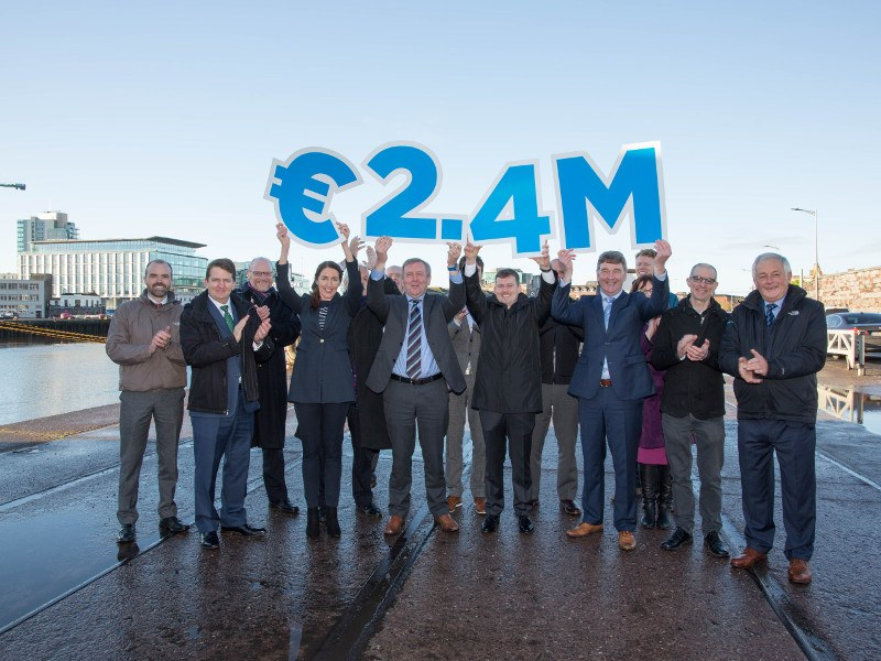 Group of people standing on a harbour holding a sign for 2.4 million euros.