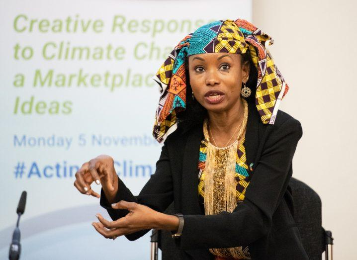 An indigenous woman in a colourful patterned dress and headpiece gestures as she speaks on stage at a climate change event.