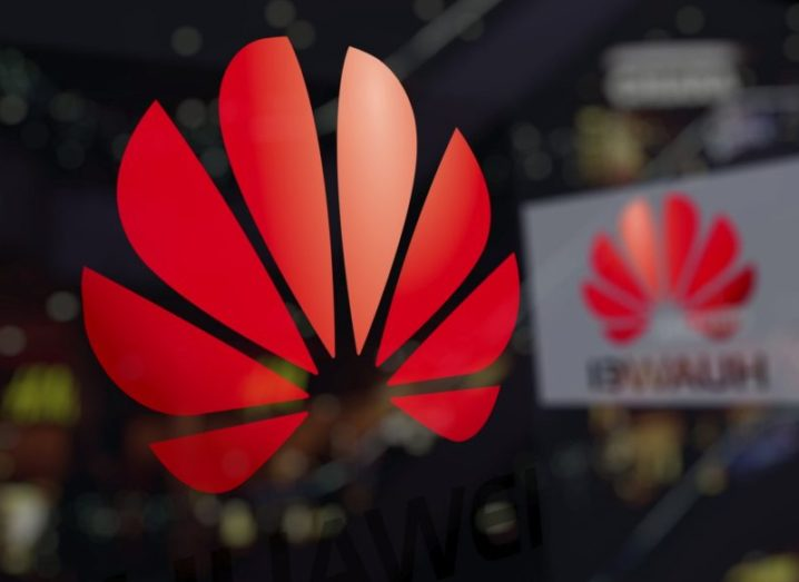 Red Huawei logo on a glass panel of an office.