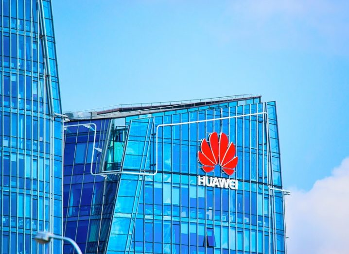 Huawei logo on a skyscraper with a blue sky in the background.