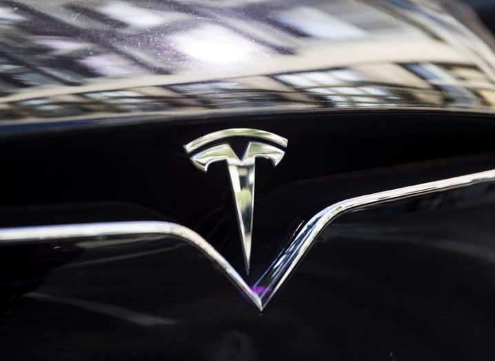 Logo detail on the front bonnet of a black Tesla electric vehicle.