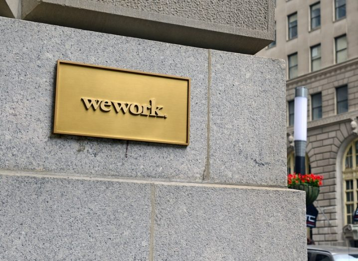 A gold plaque featuring the WeWork logo on a grey building in New York City.