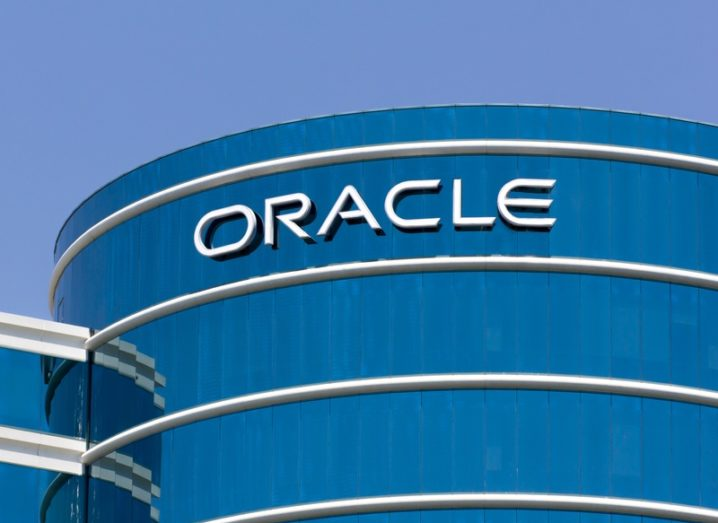 The exterior of the Oracle headquarters in Redwood, California. Cylindrical skyscraper with Oracle logo.