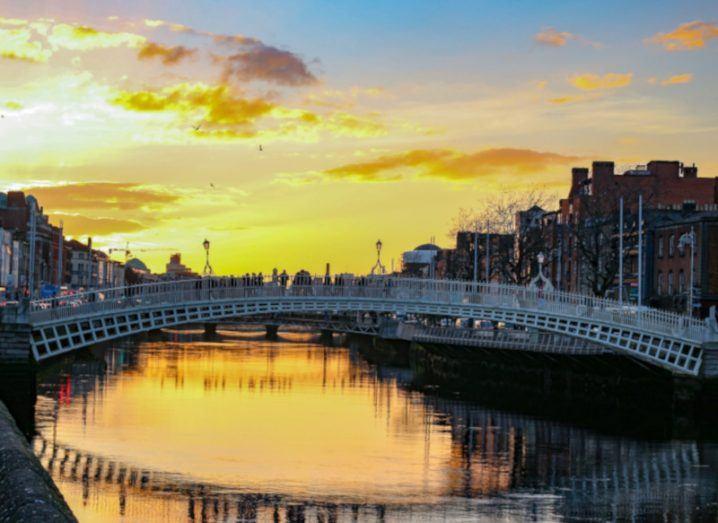 Dublin night scene with Ha'penny bridge and Liffey river lights.