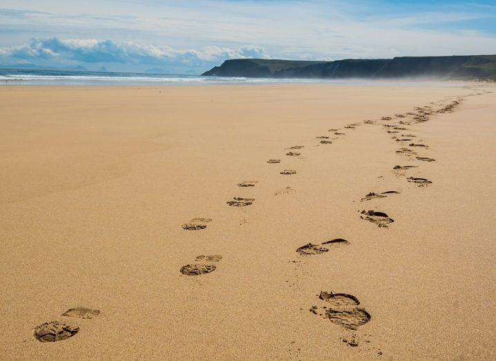 Long trail of footprints left in the sand on a beach with a cliff and clouds in the distance.
