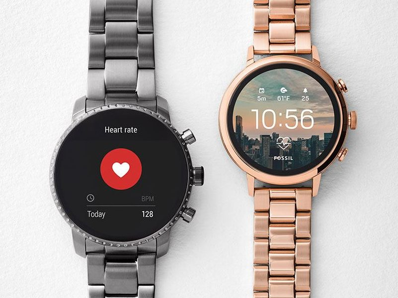 Two Fossil smartwatches. Grey metal on left with rose gold model on right, displays featuring heart rate monitors.