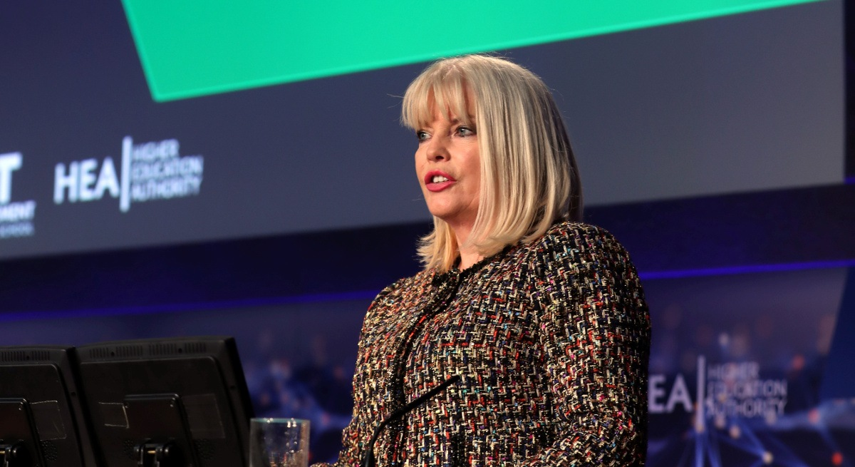 A blonde, middle-aged woman speaking at an future of work event in front of a screen. She is discussing lifelong learning.