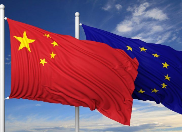 China flag alongside an EU flag under a blue cloudy sky.