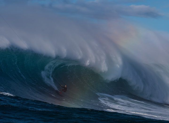 A surfer riding an enormous wave with a rainbow effect appearing in centre.