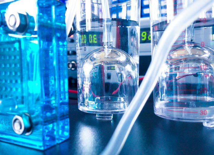 A blue hydrogen fuel cell in a lab surrounded by beakers and tubes.