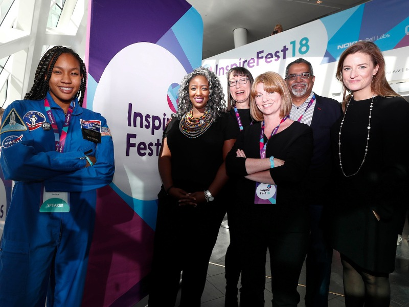 A young girl in a space camp jumpsuit, four women and an older man pose for a group photo at Inspirefest 2018.