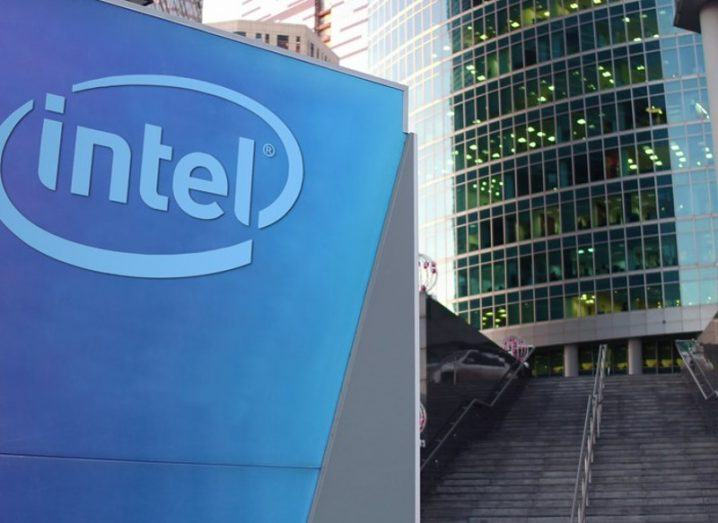 Street signage board with Intel Corporation logo in front of modern glass building.