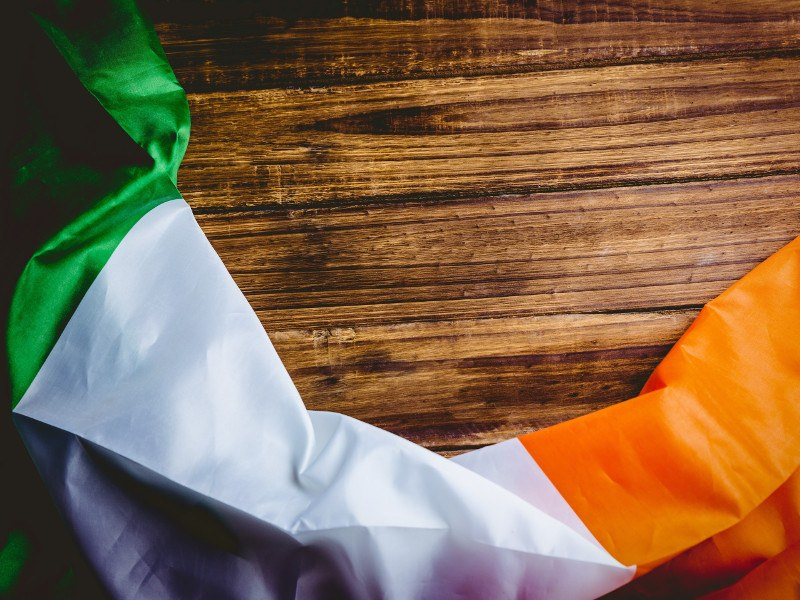 Picture of Irish flag draped across a wooden desk.