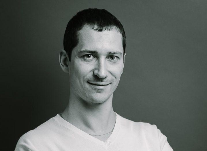 Dark-haired man in white v-necked t-shirt. Black and white photo.
