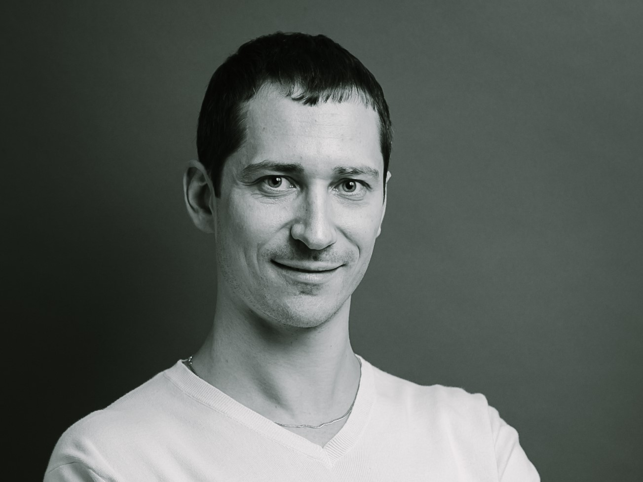 Dark-haired man in white v-necked t-shirt. Black and white photo.