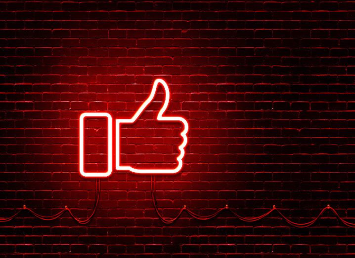 Red neon sign in shape of Facebook Like button on a brick wall.