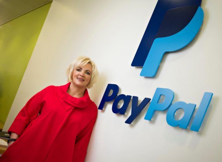 Woman in red coat with blonde hair standing in front of a PayPal sign.