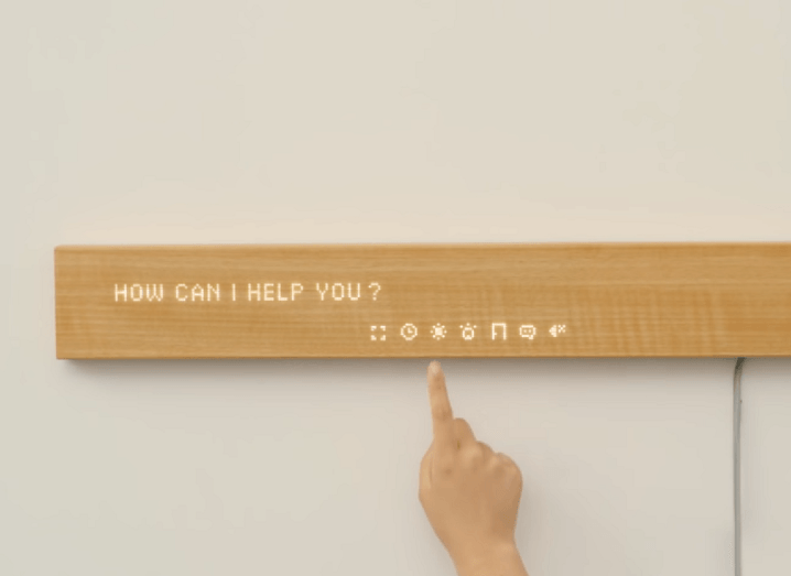 The Mui Smart Display plank of wood on a wall with a hand activating its LED screen.