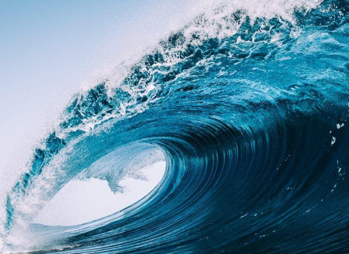 Large, blue ocean wave cresting as it approaches the shore.