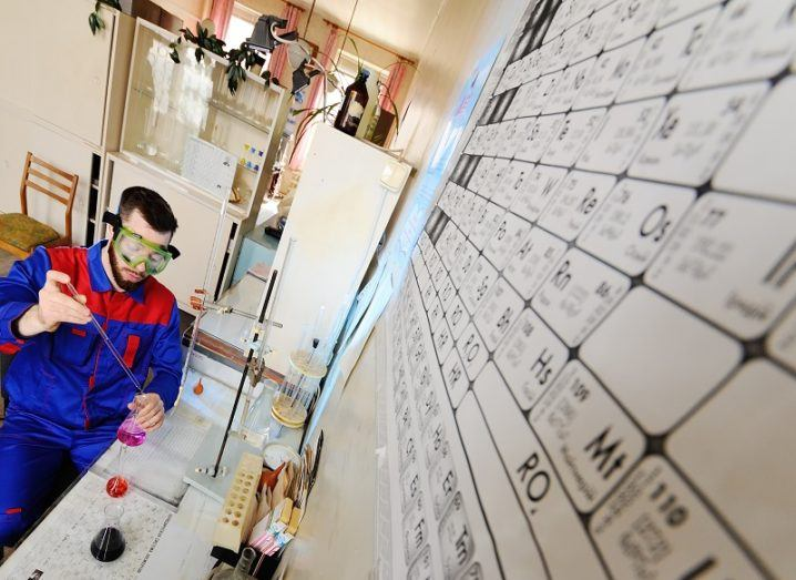 A scientist in a blue and red jumpsuit working beside a large periodic table on the wall to the right.