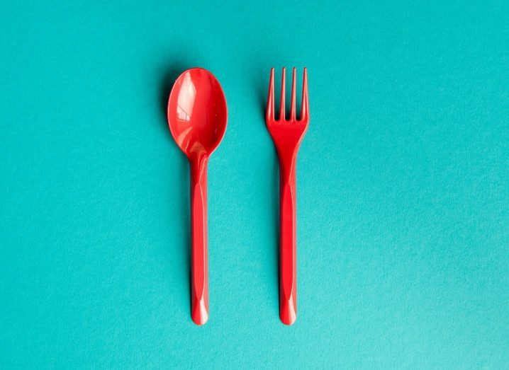 Bright red plastic fork and knife against a light blue background.