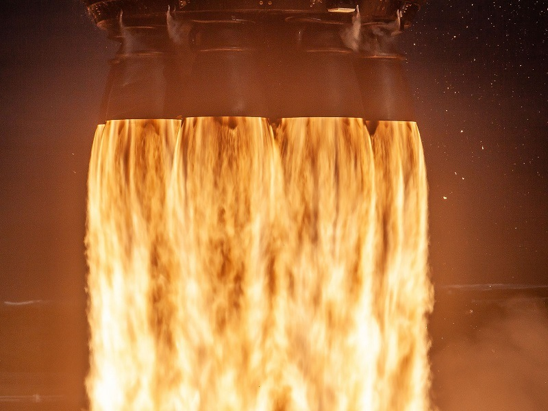 Close-up of fiery orange flames being emitted by a SpaceX rocket booster.
