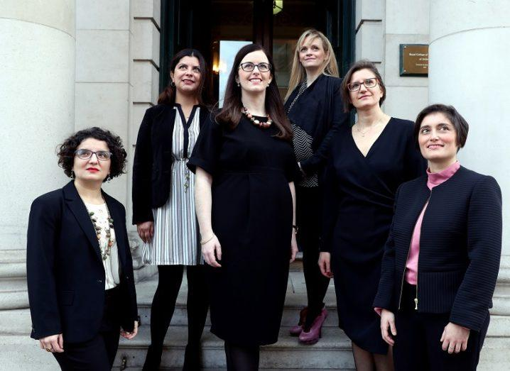 The six women researchers funded under SIRG standing and smiling on a set of steps.