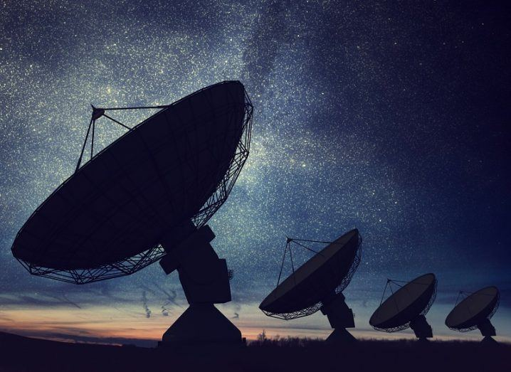 Silhouettes of four radio telescopes pointing towards starry night sky.