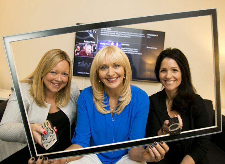 three women, two blonde and one dark haired, holding up a frame to symbolise TV. The woman in the centre is Miriam O Callaghan.