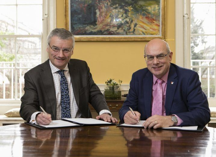 Patrick Prendergast and David Eastwood signing the agreement on a wooden desk while looking at the camera.