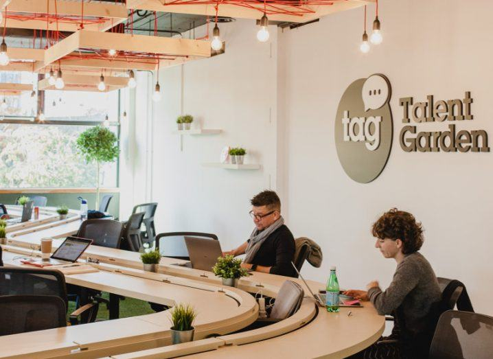 People at work around a swirl-shaped table at Talent Garden in Dublin.