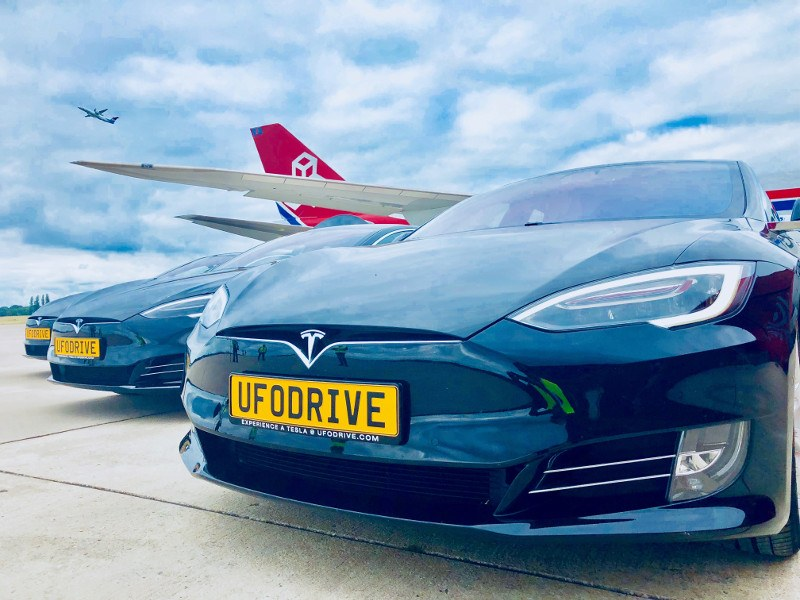 Tesla car parked in front of jet on runway.