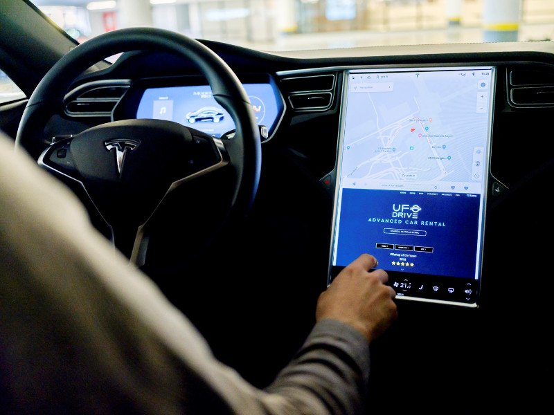 Driver using touch screen in Tesla saloon.