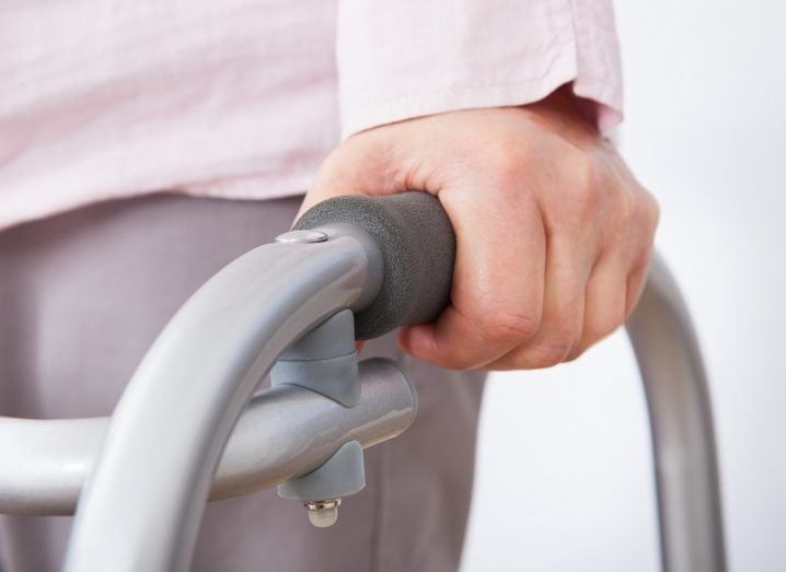 Closeup of elderly woman with walking frame against white background.