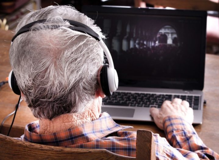 Back of an older man's head wearing headphones as he uses a laptop computer.